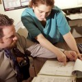 Detective Nixon (Mark Galineau) and Dr. Murphy (Lissa Bouchard) examine some evidence  in 'The Zahsman Murders.'
