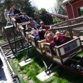 Families take a ride on a rollercoaster at Happy Hollow Zoo.