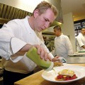 Chef Matthias Froeschl prepares a plate of pork belly and halibut at Campbell's new Naschmarkt restaurant.