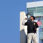 """As the rich get richer, Shaun """"Cracker"""" O'Kelly's scaling of a 36-foot wall at San Jose's City Hall has elevated the prominence of the issue locally. (Photo by Felipe Buitrago)"""