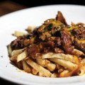 POUTINE: This simple dish consists of French fries layered with squeaky cheese curds and beef gravy.