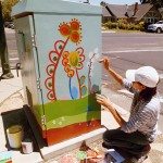 Artist Florence de Bretagne works on a new art box at the junction of Pine Street and Lincoln Street.`