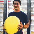 BIG CHEESE: Brian shows off one of the Milk Pail's popular cheese wheels. Photograph by Alex Stover