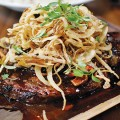 STAKE YOUR CLAIM: The ginger ponzu ribeye steak comes with a load of sriracha-laced onion strings. Photo by Ngoc Ngo