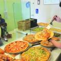 Sweet Sicily employee Dimitri Ramirez serves homemade pizza to regular patron Chuck Catania. (Photo by Robert Eliason)