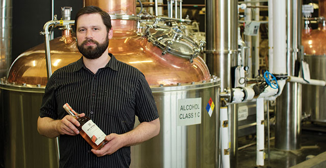 BEST SHOT: Brand ambassador Ryan Hummel stands with a bottle of 10th St. Distillery's flagship product: an aged, peated whiskey. Photo by John Dyke